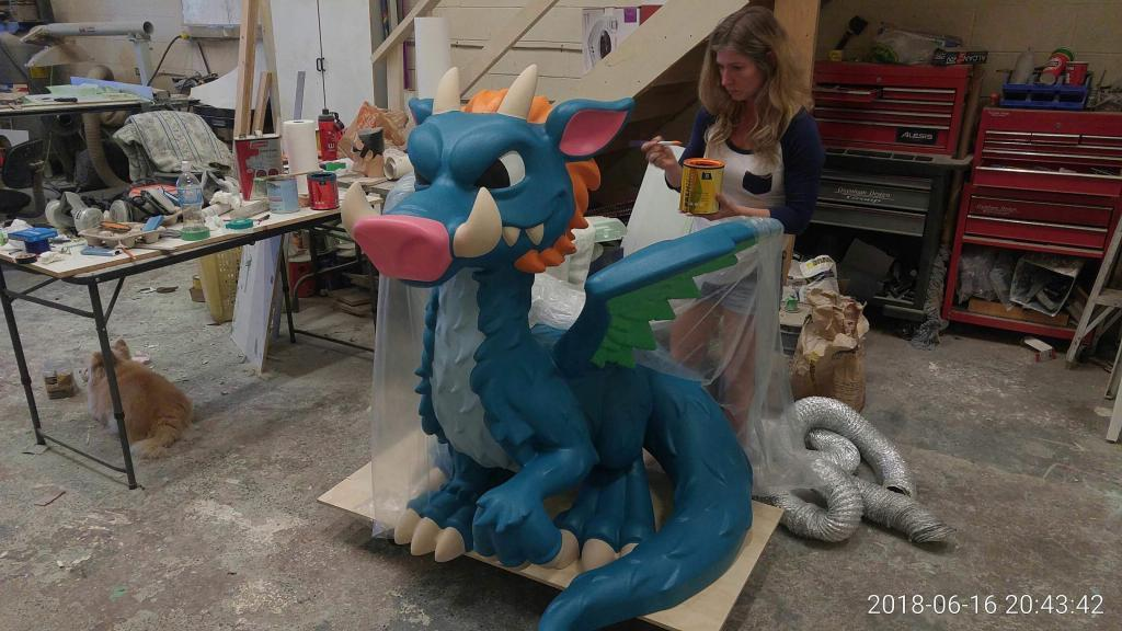 Woman Painting Blue Dragon That was Created Using A Techno CNC Router Machine. Has An Orange Cat Hiding Under A Table.